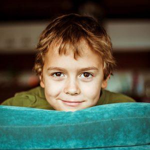 Junge schaut ueber ein Sofa in die Kamera